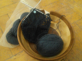 Lace knitting on a circular needle, done in navy blue yarn. The knitting and ball of working yarn is inside a wooden yarn bowl.  There is a small blue disk stitch marker clipped into the work.  A twisted skein of yarn is beside the yarn bowl.