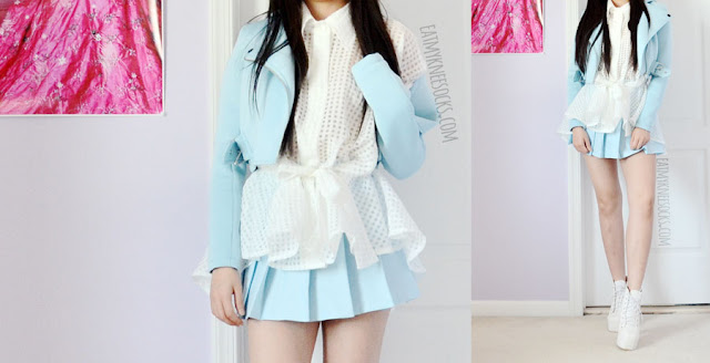 Details on the white batwing semi-sheer gridded buttoned shirt top from Twist X Turn, worn with a pleated pastel baby blue tennis skirt and cropped light blue moto jacket.