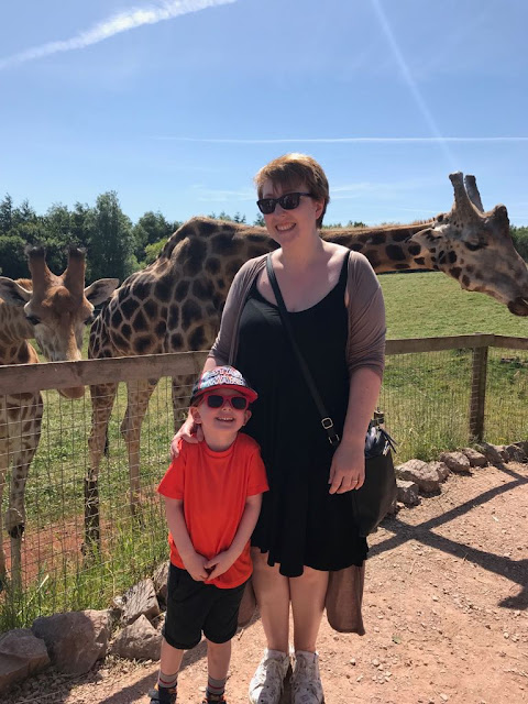 Mum and son standing next to a giraffe