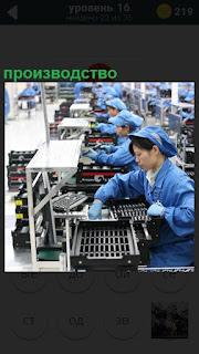 На конвейере сидят девушки и собирают продукцию на производстве