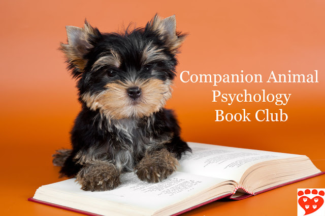 A puppy reads a book about dogs and cats