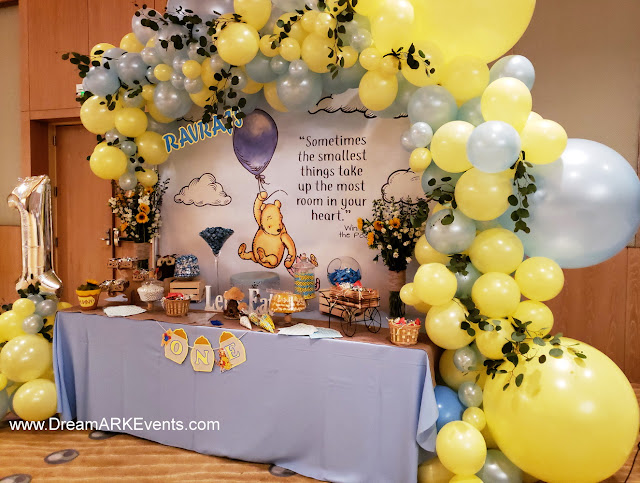 Blue & pastel yellow organic balloon arch with themed custom banner