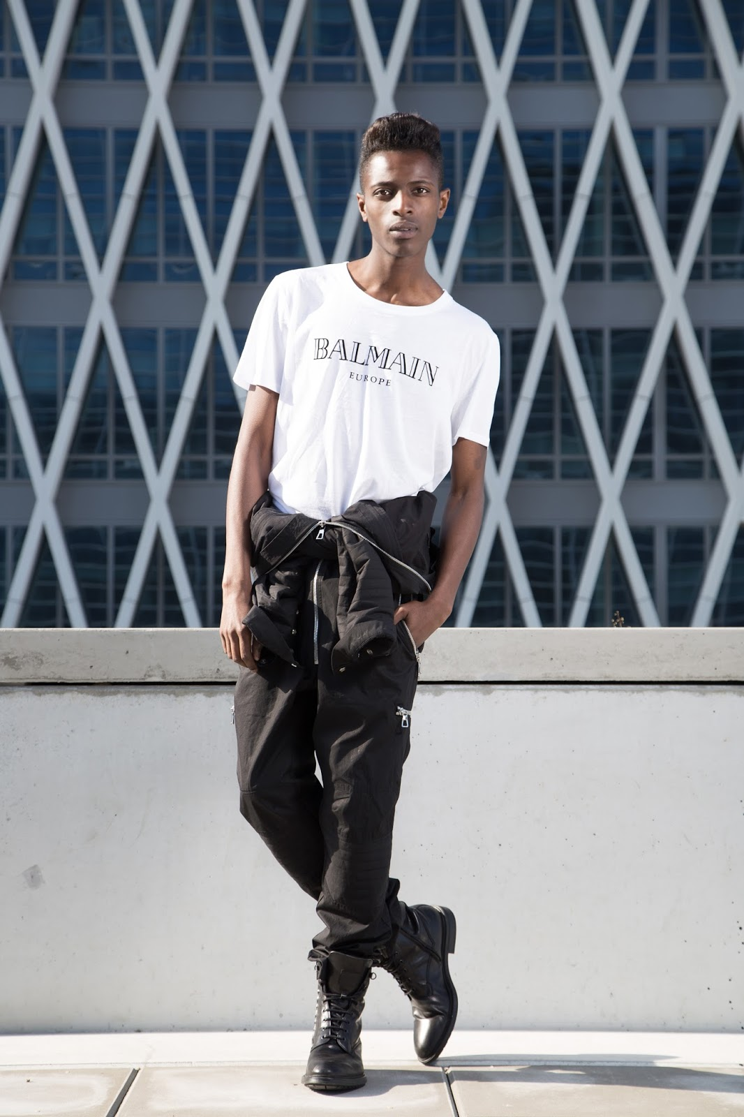 Introducing you Balmain x H&M men's collection + street style guide for Balmain x H&M men's collection written by jonthegold / photography by HOYmedia ( antwerp ) wearing black jump suit and white balmain europe tshirt and HUGO by hugo boss shoes