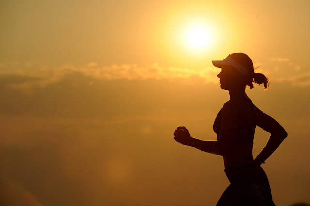 A silhouette of a woman running at sunset