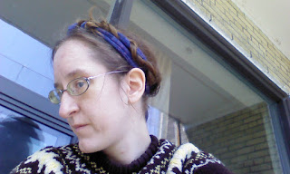 A woman standing next to a window with her hair up around her head in braids. The braids have a purple scarf worked into them.
