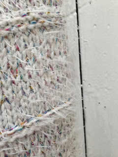 Really close up detail of the rainbow thread on the cream jumper