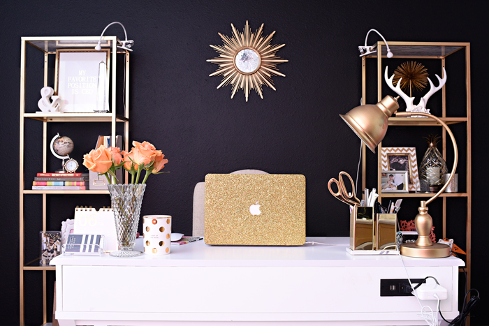 A black, white and gold home office featuring a fab IKEA VITTSJO hack, tricorn black walls, a sunburst mirror, white desk and other glam home decor accents.