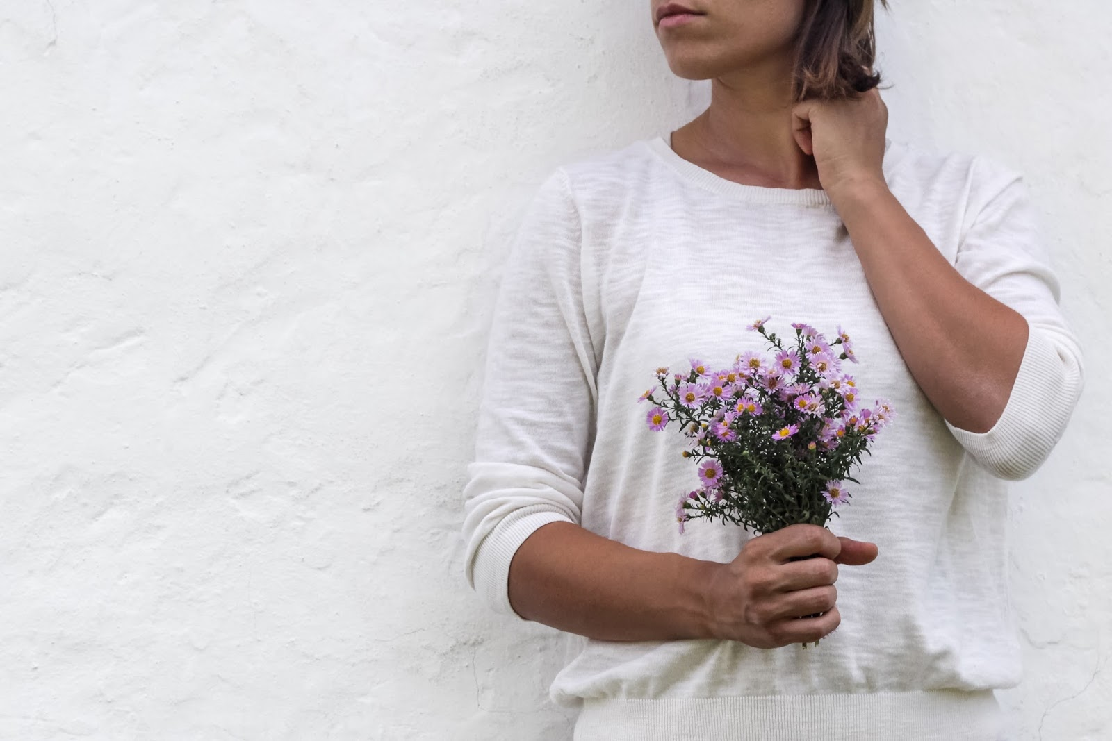 Mother Distracted Problem Page: Woman in white tunic, leaning against a white wall holding a bunch of pink flowers