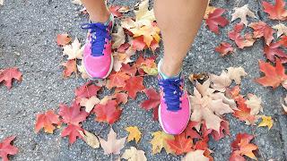 Jambes de coureuse, espadrilles de course New Balance, feuilles d'érable colorées, asphalte