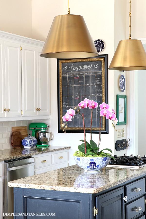 brass pendants, savoy alden pendant, chalkboard calendar, green kitchen aid mixer, orchid arrangement