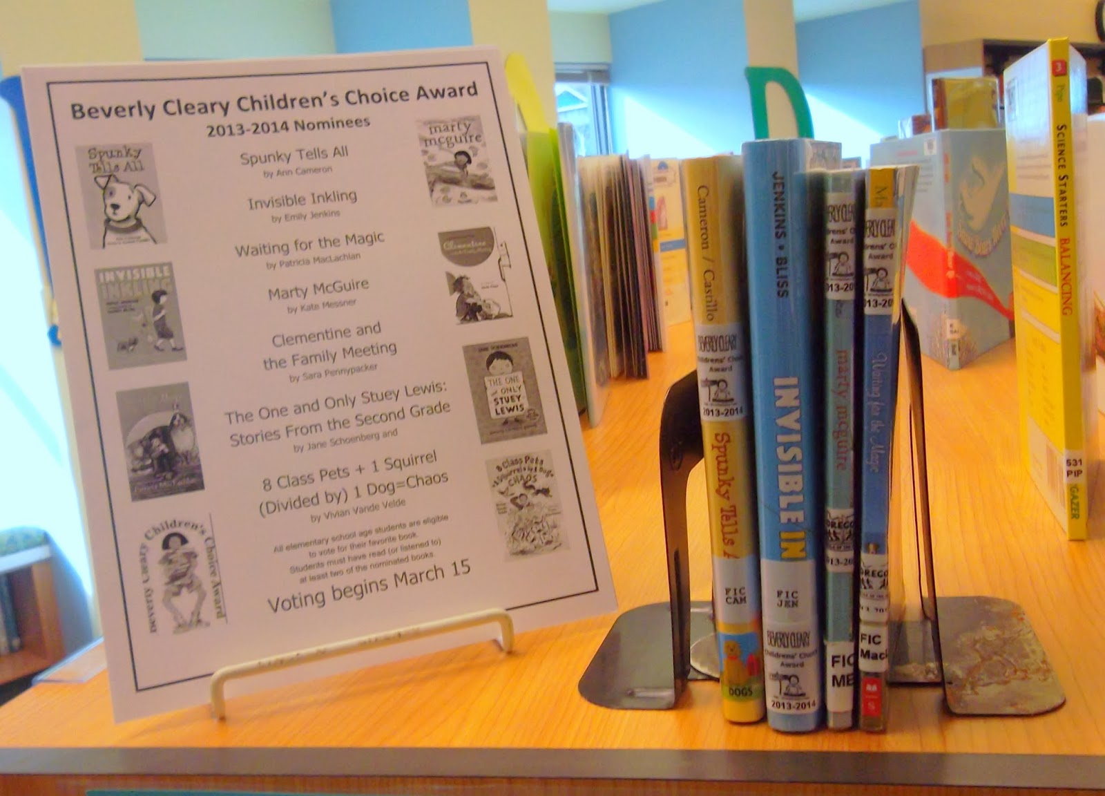 A poster held up by a wire stand displays cover art and lists titles and authors for Beverly Cleary Children's Choice nominees: Spunky Tells All by Ann Cameron, Invisible Inkling by Emily Jenkins, Waiting for the Magic by Patricia MacLachlan, Marty McGuire by Kate Messner, Clementine and the Family Meeting by Sara Pennypacker, The One and Only Stuey Lewis: Stories From the Second Grade by Jane Schoenberg and 8 Class Pets + 1 Squirrel (Divided by) 1 Dog=Chaos by Vivian Vande Velde . To the poster's right, four books -- Spunky Tells All, Invisible Inkling, Marty McGuire and Waiting for the Magic -- are shelved between bookends. Each book has a Beverly Cleary award label on its spine.