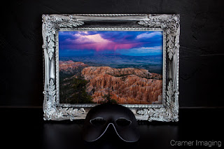 "Cramer Imaging's photograph of a framed ""Into the Storm"" with a black mask against a black gallery wall"