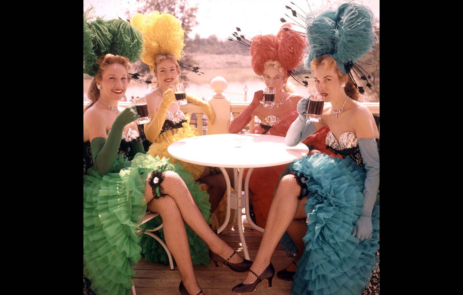 Showgirls in costume sit at an outdoor table and drink from mugs at Disneyland in July 1955.