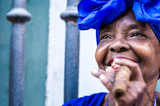 A older Cuban woman with a blue head wrap smoking a Cuban cigar. She is smiling with the cigar held between fingers of her left hand. In the background there is a iron fence in front of a blue and white building.