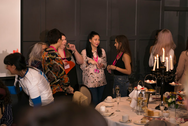 Photo of myself, standing and talking with other bloggers who are at the girls day out blogger event. I have long dark hair, a pink floral shirt and some blue jeans on
