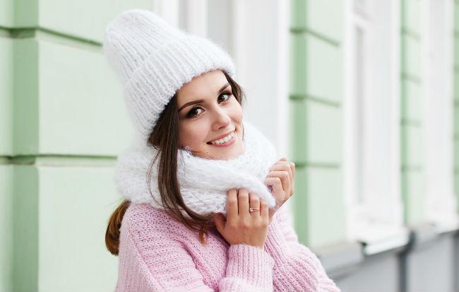 Ragazza con sciarpa e cappello che si protegge dai primi freddi autunnali