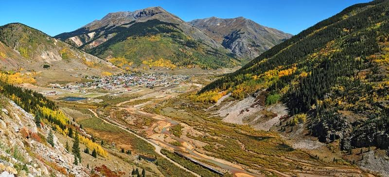 "Fascinating view down to Silverton along the San Juan Skyway. Close to the lower rim you can see the ""Durango & Silverton Narrow Gauge Railroad Train"" heading northwest to the city."