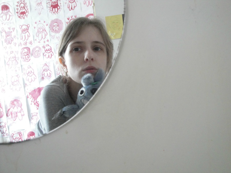 A picture of me, again seen in the circular mirror, holding a small Totoro toy.