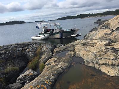 Pieni kumivena ja hieman isompi vene kalliorannassa.