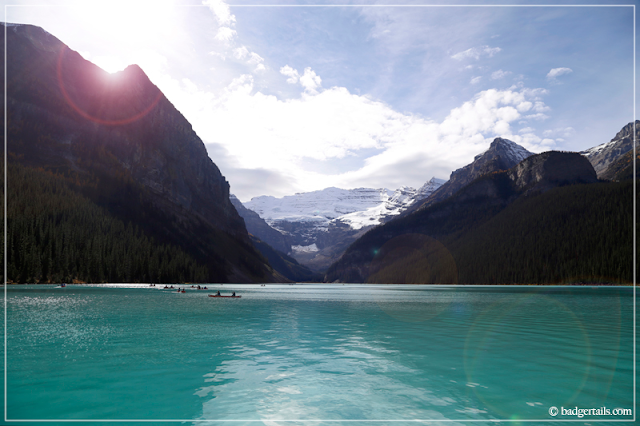 Lake Louise with Sun Shining round the Mountain and Pure Blue Water. > See more on Badgertails.com <