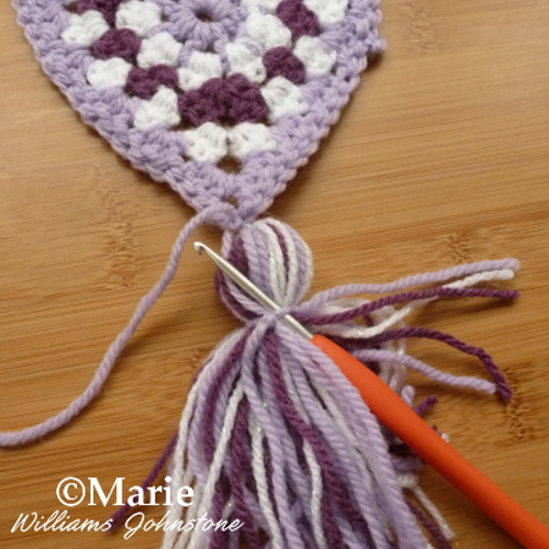 Tidying up the strands of crocheted bunting banner with a crochet hook