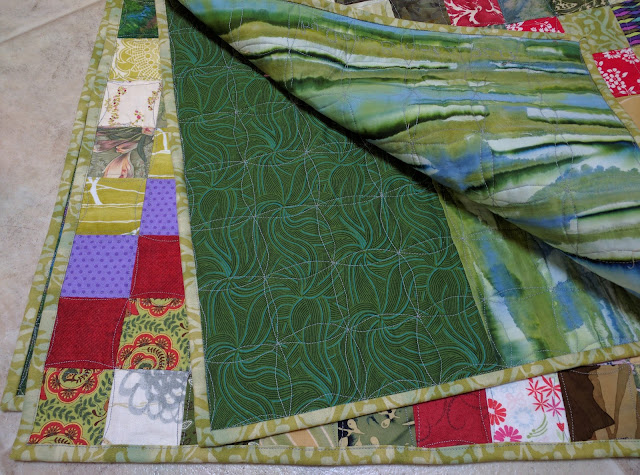 Binding is a medium green print on this Scrappy Trip Around the World quilt