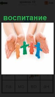 Ладони рук ограждают фигурки в качестве воспитания детей, которые держатся за руки