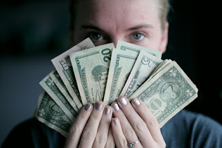 Person holding fan of U.S. dollars banknotes - Source: Unsplash, Sharon McCutcheon - https://unsplash.com/photos/rItGZ4vquWk