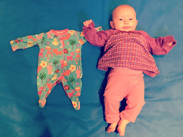 A newborn sleep suit next to a 3 year old baby