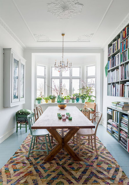 This area rug anchors the dining table beautifully and all those books make this space extra inviting- design addict mom