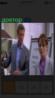 """Фрагмент из фильма """"Доктор Хаус"""" стоит рядом с женщиной около доски"""