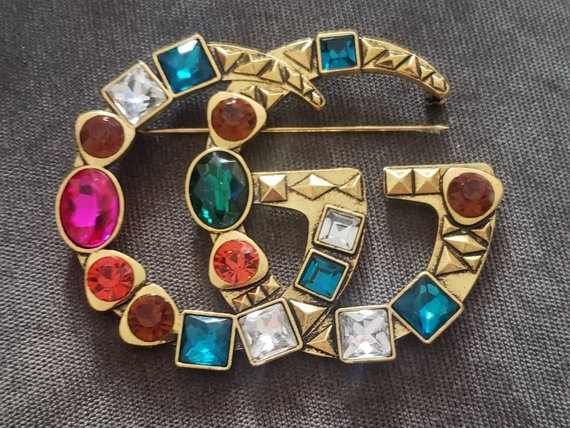 1bac921d52f Starting with this replica Gucci multi colored rhinestone GG brooch it s  pretending to be