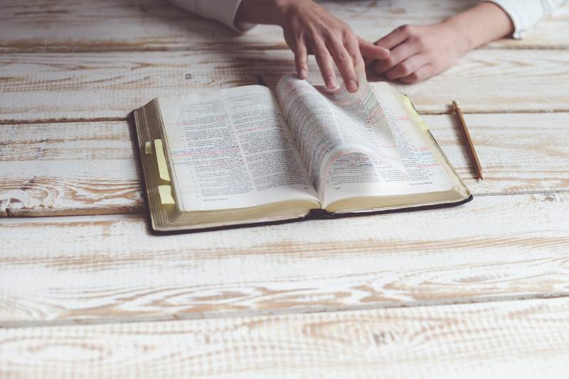A person reading through the Bible sat at a table.