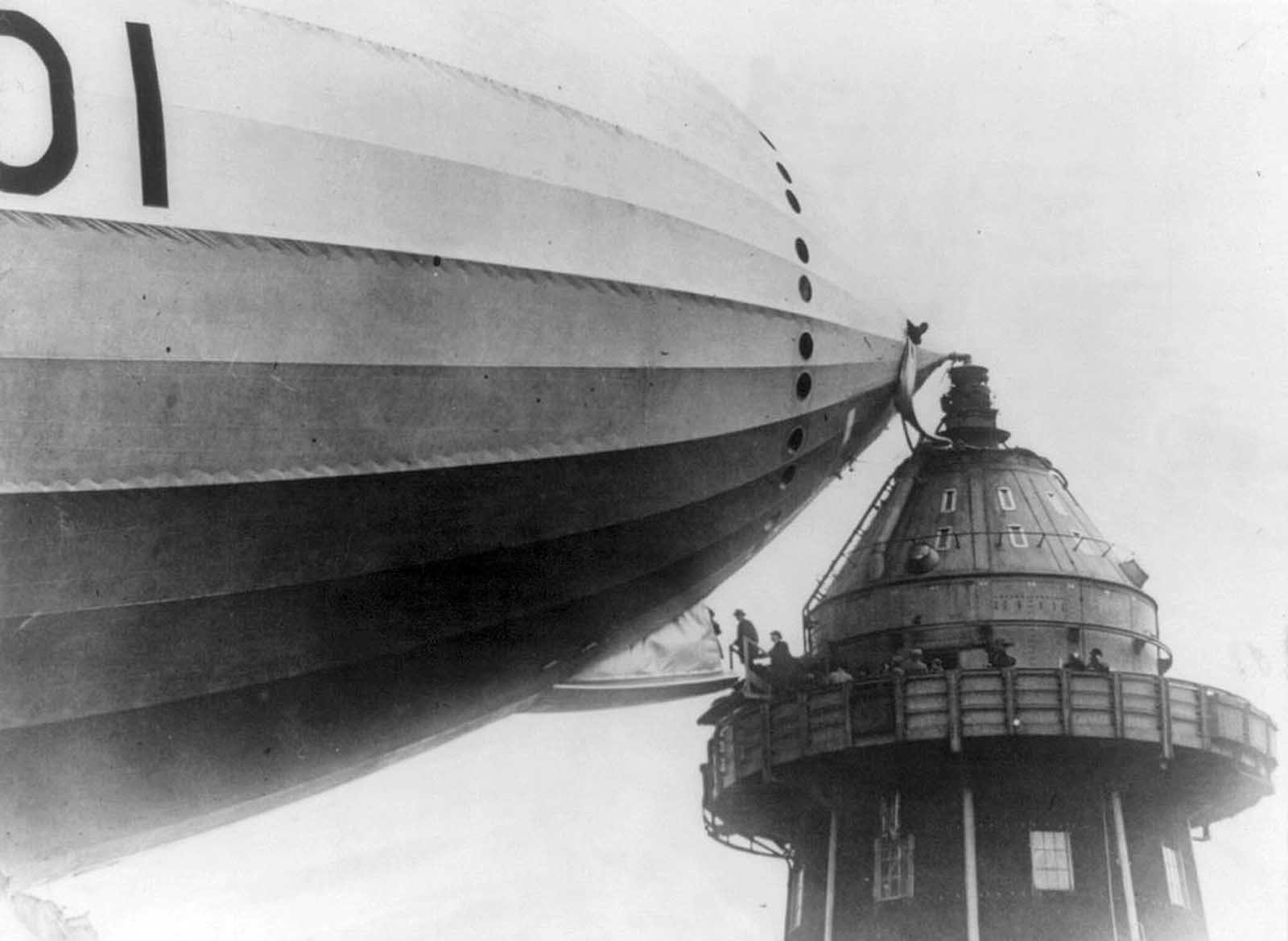 British M.P.s walk onto an airship gangplank, in Cardington, England, in the 1920s.