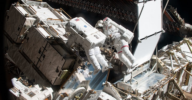 Spacewalkers and NASA astronauts Christina Koch and Nick Hague (suit with red stripe on legs) retrieve hardware from a pallet delivered on the Japan Aerospace Exploration Agency's (JAXA) HTV-7 (H-II Transfer Vehicle-7) to continue upgrading the International Space Station's power storage capacity. The duo worked outside in the vacuum of space for six hours and 45 minutes to continue swapping batteries and install adapter plates on the station's Port-4 truss structure. Credit: NASA