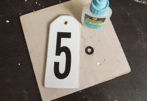 Gluing spray painted washers onto distressed number tags.