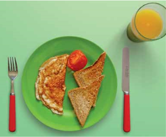 Omelet with grilled tomato and toast and a small glass of orange juice