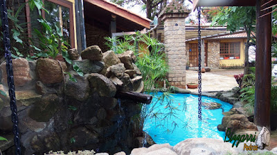 Detalhe da varanda do restaurante Recanto das Pedras com o lago de carpas com pedras ornamentais com o fundo do lago pintado de azul e nas fachadas as paredes de pedra com os pilares de pedra com o pergolado de madeira.