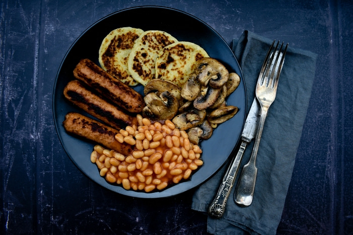 Vegan cooked breakfast with potato scones including veggie sausages, baked beans and mushrooms
