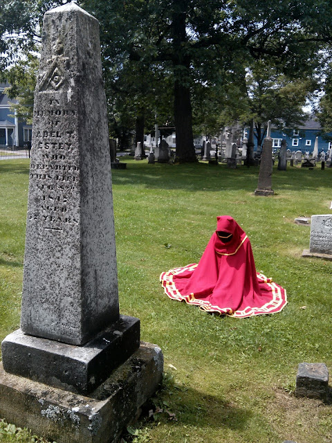 T wearing a Journey costume, meditating before an obelisk