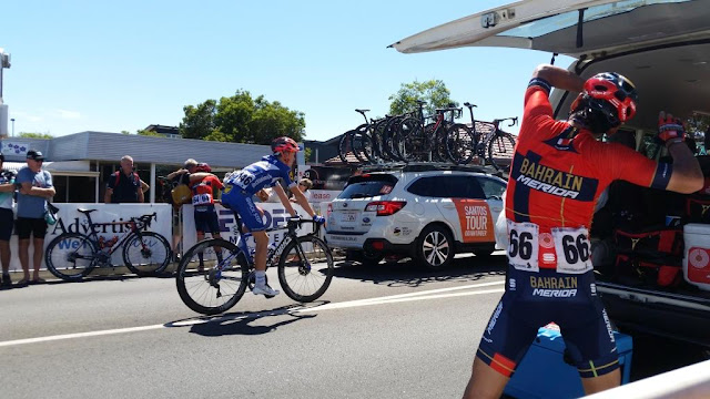 Foreground at right: Domenico Pozzovivo in red Bahrain Merida colours has his arms raised as he bends his body to do warm up stretches in the shade of the bus tailgate.  In the middle, James Knox in the blue Deceunninck-Quickstep colours is riding from left to right towards the starting line. In the background, against the barrier fencing, there are bikes leaning while Heinrick Haussler has his back to us as he takes photos arm in arm with a spectator.