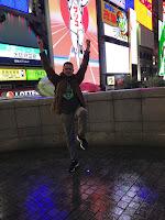 Carlos haciendo de Glico Man con carteles publicitarios y luminosos detrás