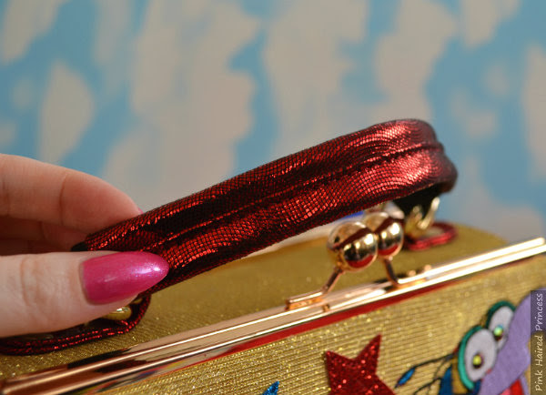 hand showing red metallic fabric used on handle of bag