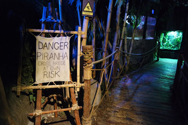 wooden bridge with 'danger, piranha!' sign