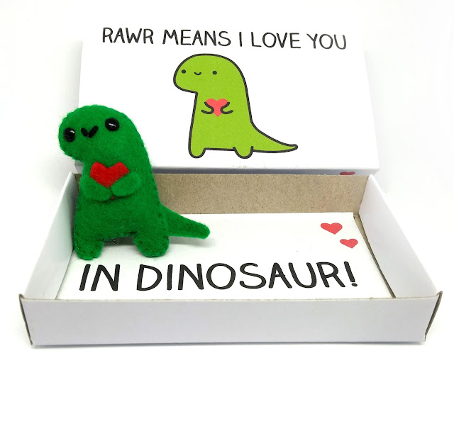 An image from the Etsy store selling a cute mini felt dinosaur magnet holding a heart which comes in a matchbox with the text Rawr means I love you in dinosaur