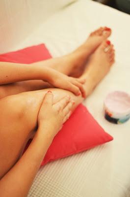 Aplicándose anticelulítico en las piernas