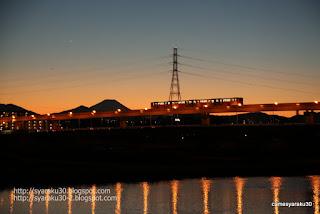 夕暮れの多摩川を渡るモノレール写真
