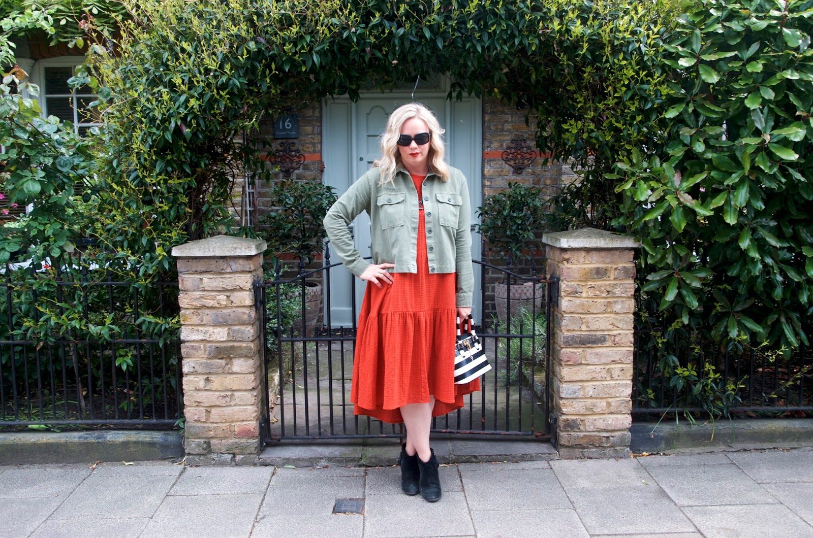 Orange dress, green jacket and striped bag