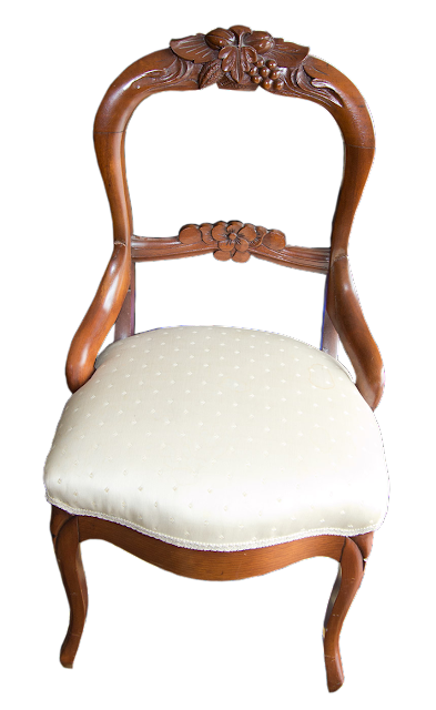 Another Victorian chair, this one open-backed and carved from walnut, covered in an off-white silk fabric.