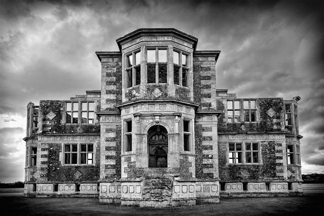 Atmospheric black and white image of Lyveden New Bield under stormy skies